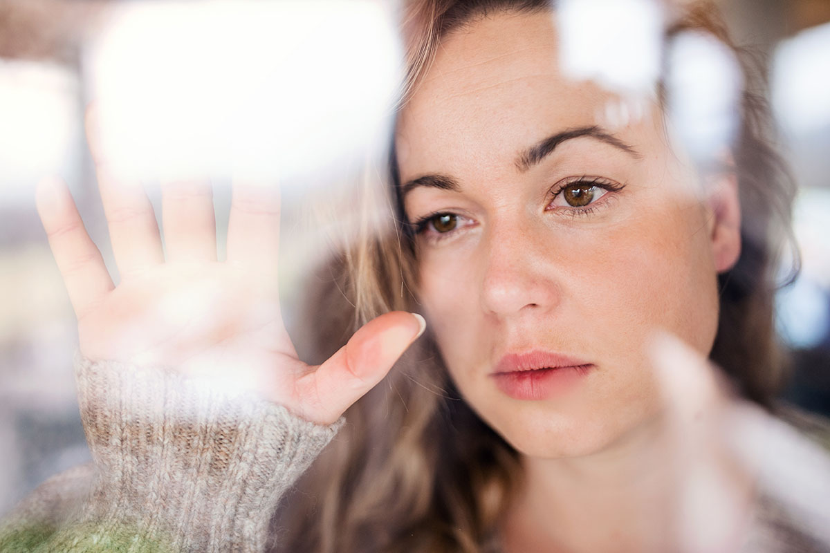 a woman stares pensively out the window with her hand up against glass as she thinks about depression treatment during covid 19