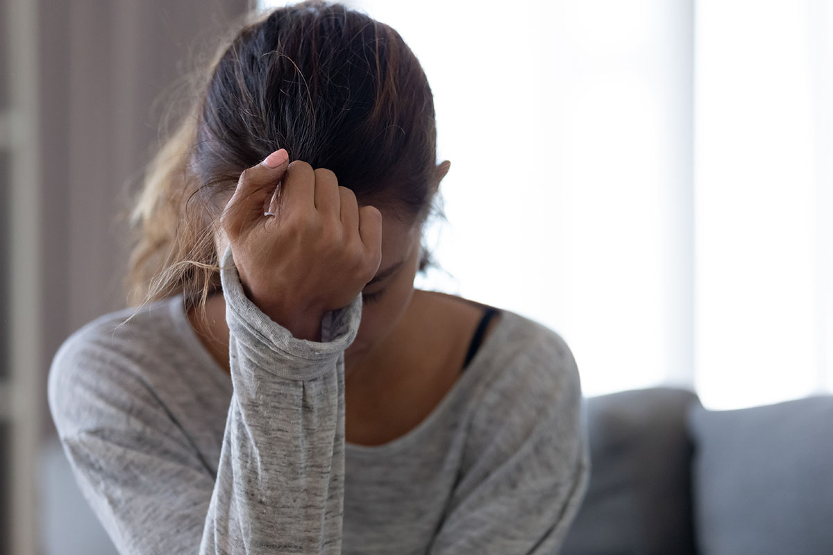 a woman rests her head against her wrist as she struggles with the signs of anxiety